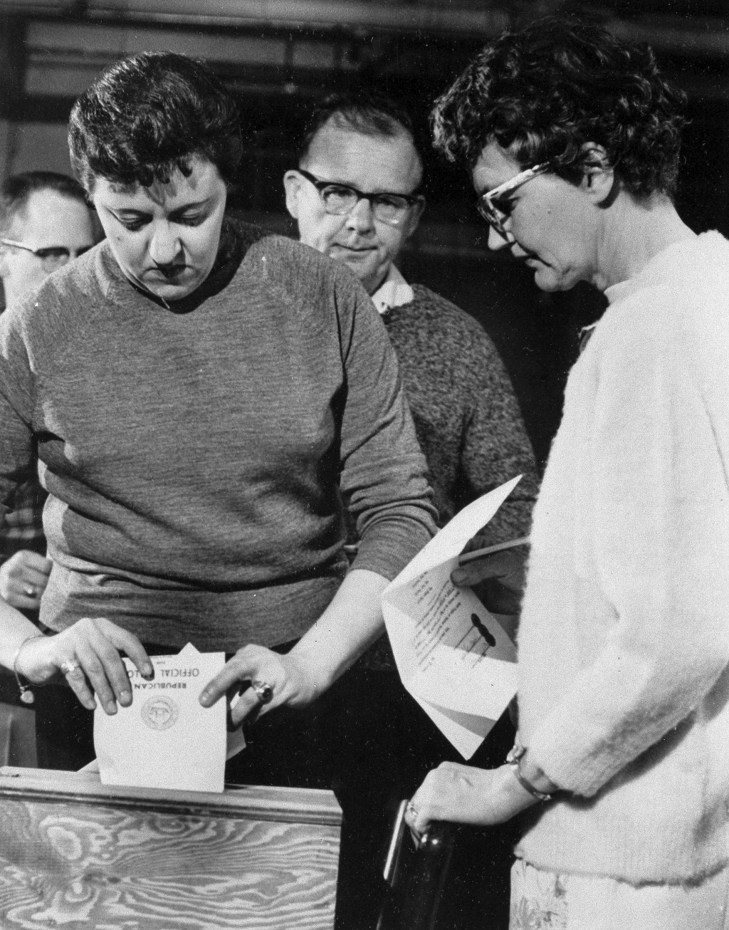 FILE - In this March 10, 1964, file photo, Laraine Jolin, left, casts her ballot in the New Hampshire primary moments after midnight as town clerk and...