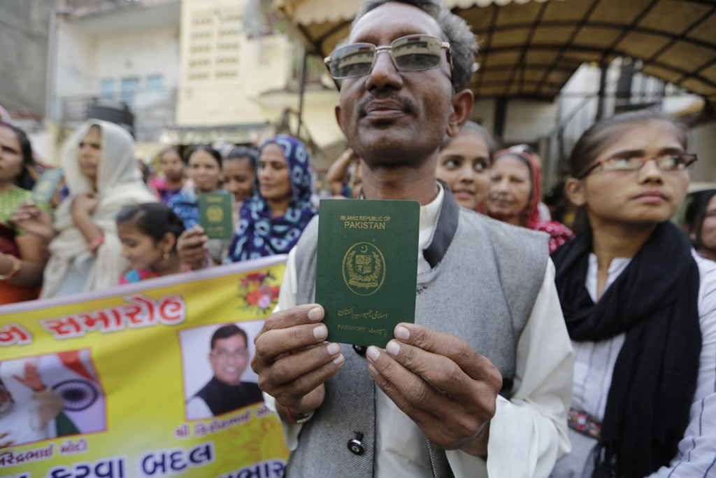 Hindu refugee Mohan Ranva who migrated from Sindh province of Pakistan holds his passport as he along with otherssupport the Citizenship Amendment Act...