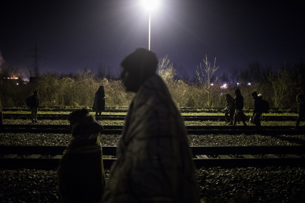 In this picture taken Tuesday Dec. 17, 2019, a group of migrants wander around the rail tracks near the river Drina bordering between Bosnia and Serbi...