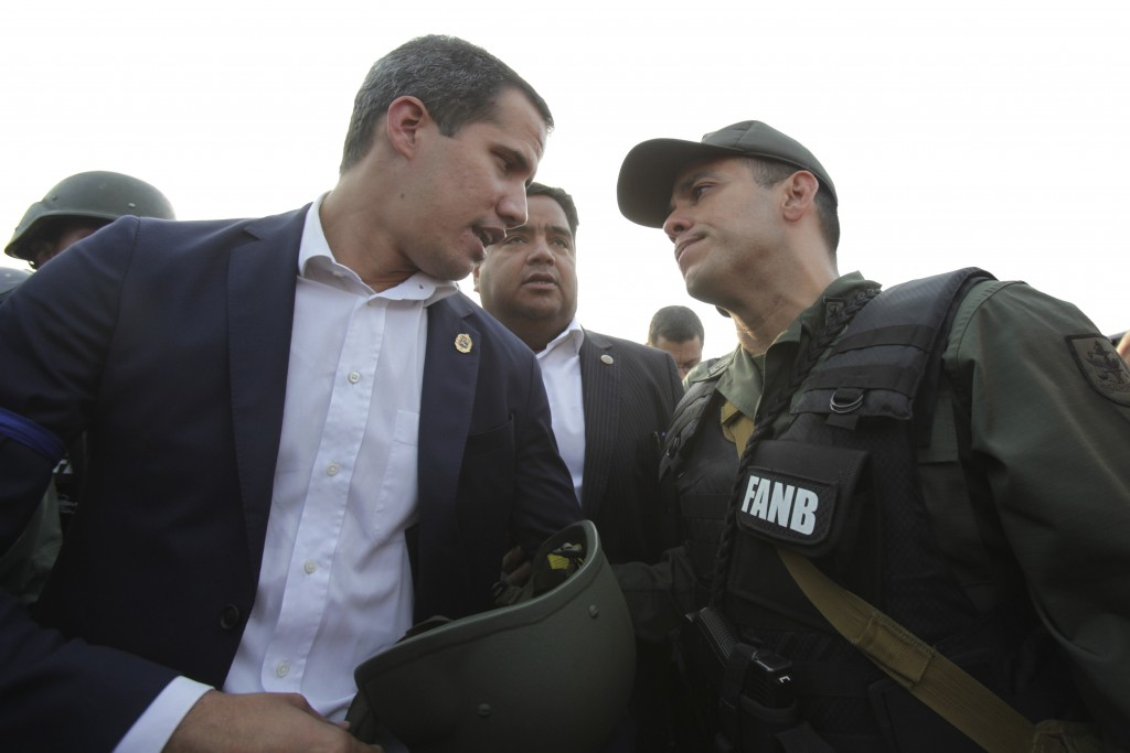 FILE - In this April 30, 2019 file photo, Venezuela's opposition leader and self-proclaimed president Juan Guaido talks to an Army officer outside La ...