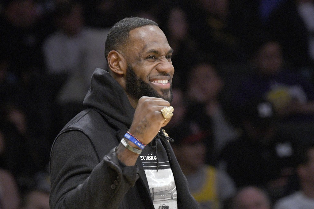Los Angeles Lakers injured guard LeBron James cheers his team during the first half of an NBA basketball game against the Denver Nuggets on Sunday, De...