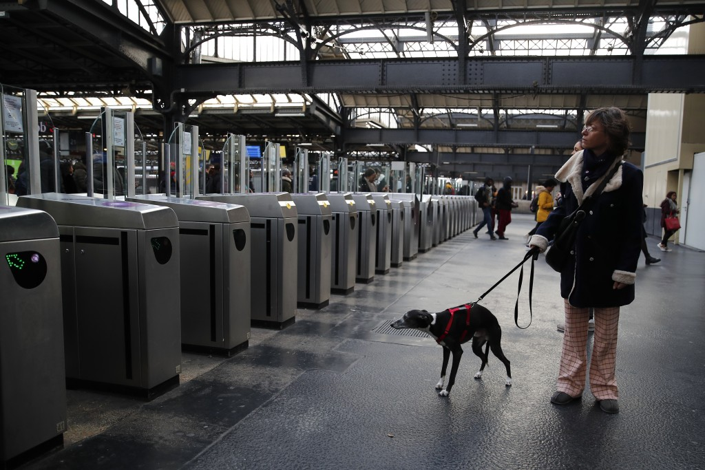 A woman walks her dog at the empty Gare de l'Est train station Monday, Dec. 23, 2019 in Paris. France's punishing transportation troubles may ease up ...