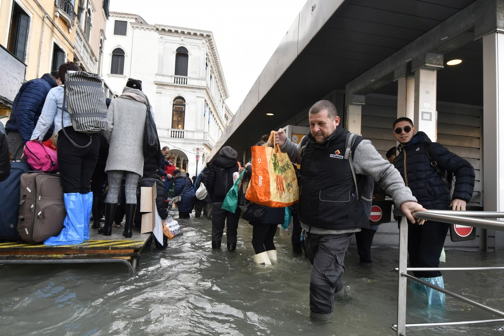 People stand on a trestle bridge as others wade through water during a high tide of 1.44 meters (4.72 feet), in Venice, Italy, Monday, Dec. 23, 2019. ...