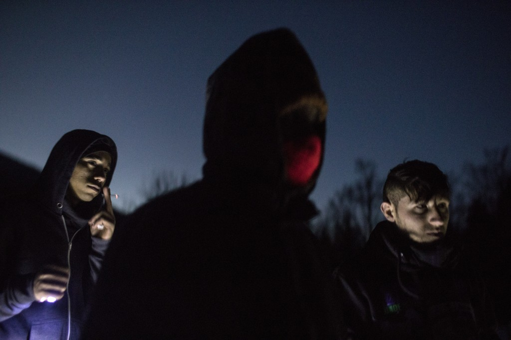 In this picture taken Saturday Dec. 14, 2019, Afghan migrants stand near an abandoned farm located in the Bosnian side of the mountains near the borde...