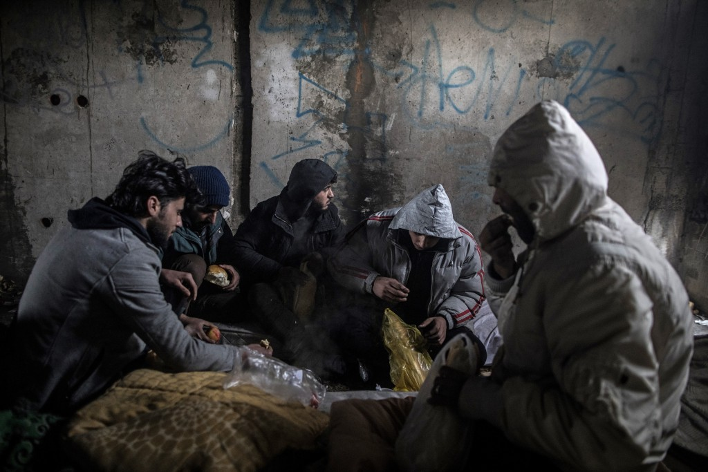 In this picture taken Saturday Dec. 14, 2019, a group of Syrian migrants have breakfast inside an an abandoned building as they take shelter before ma...