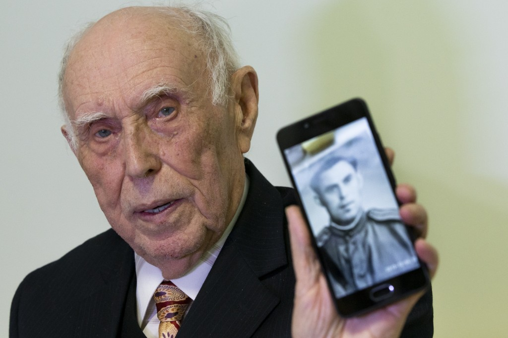 Holocaust survivor WWII veteran Mikhail Spectr, 86, shows a photo of him in Soviet Army officer's uniform to the media at the annual Hanukkah Menorah ...