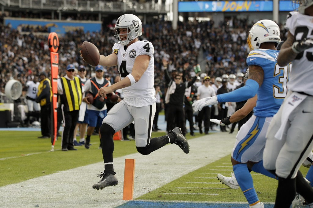 Oakland Raiders quarterback Derek Carr scores against the Los Angeles Chargers during the first half of an NFL football game Sunday, Dec. 22, 2019, in...