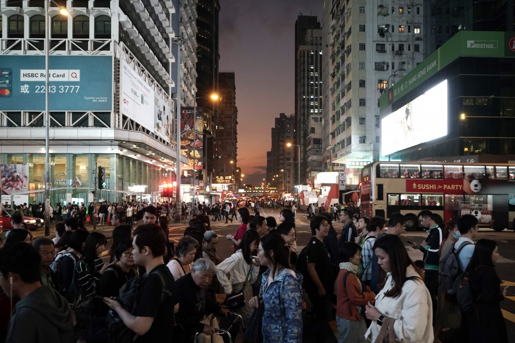 In this Wednesday, Dec. 18, 2019 photo, people cross a main street in Mongkok, a shopping district of Hong Kong. Sellers of luxury goods that are easi...