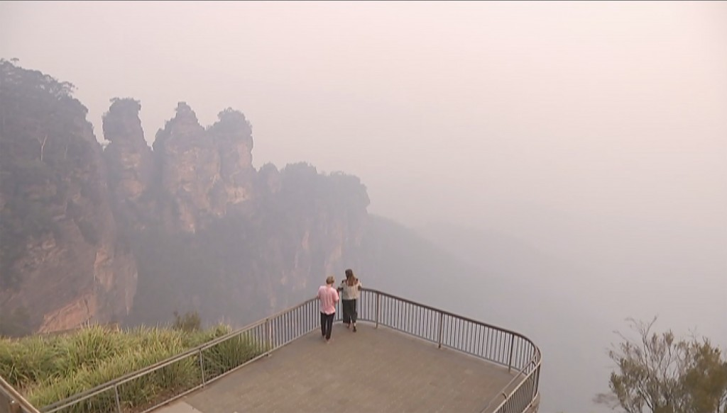 In this image made from video, two people watch from a look out of smoke from wildfire, Monday, Dec. 23, 2019, in the Blue Mountains, New South Wales,...