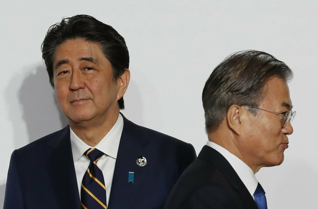 FILE - In this June 28, 2019, file photo, South Korean President Moon Jae-in, right, walks by Japanese Prime Minister Shinzo Abe upon his arrival for ...