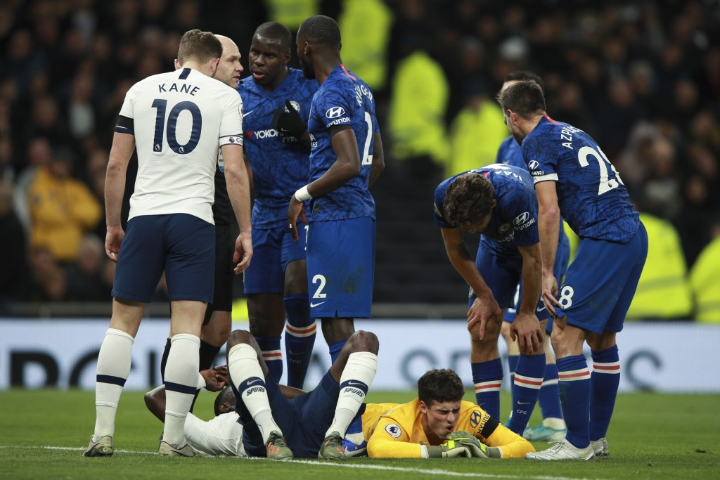 Chelsea's goalkeeper Kepa Arrizabalaga lies on the pitch next to Tottenham's Moussa Sissoko after clashing, during the English Premier League soccer m...