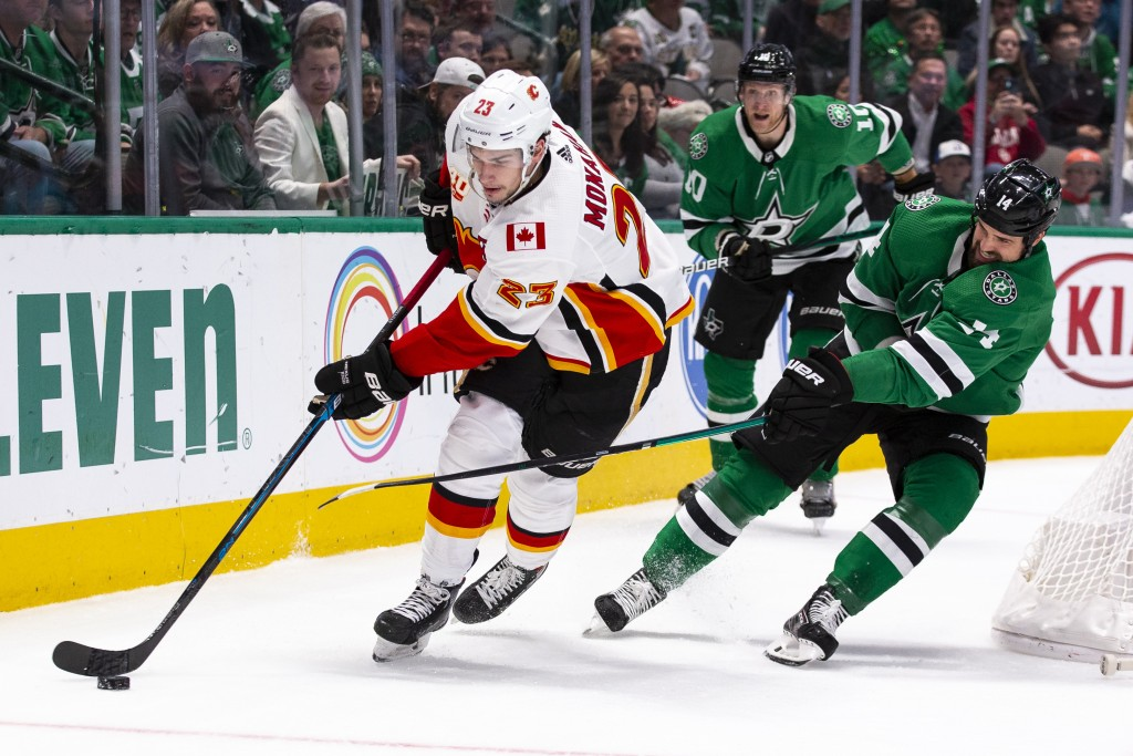 Calgary Flames center Sean Monahan (23) skates with the puck behind the net as Dallas Stars left wing Jamie Benn (14) defends during the first period ...