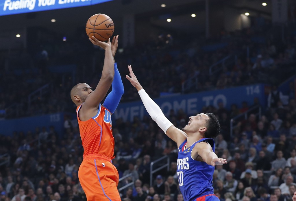 Oklahoma City Thunder guard Chris Paul, left, shoots as Los Angeles Clippers guard Landry Shamet (20) defends during the second quarter of an NBA bask...