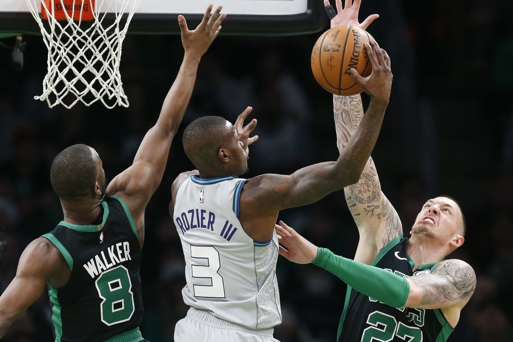 Boston Celtics' Kemba Walker (8) and Daniel Theis (27) defends against Charlotte Hornets' Terry Rozier (3) during the first half of an NBA basketball ...