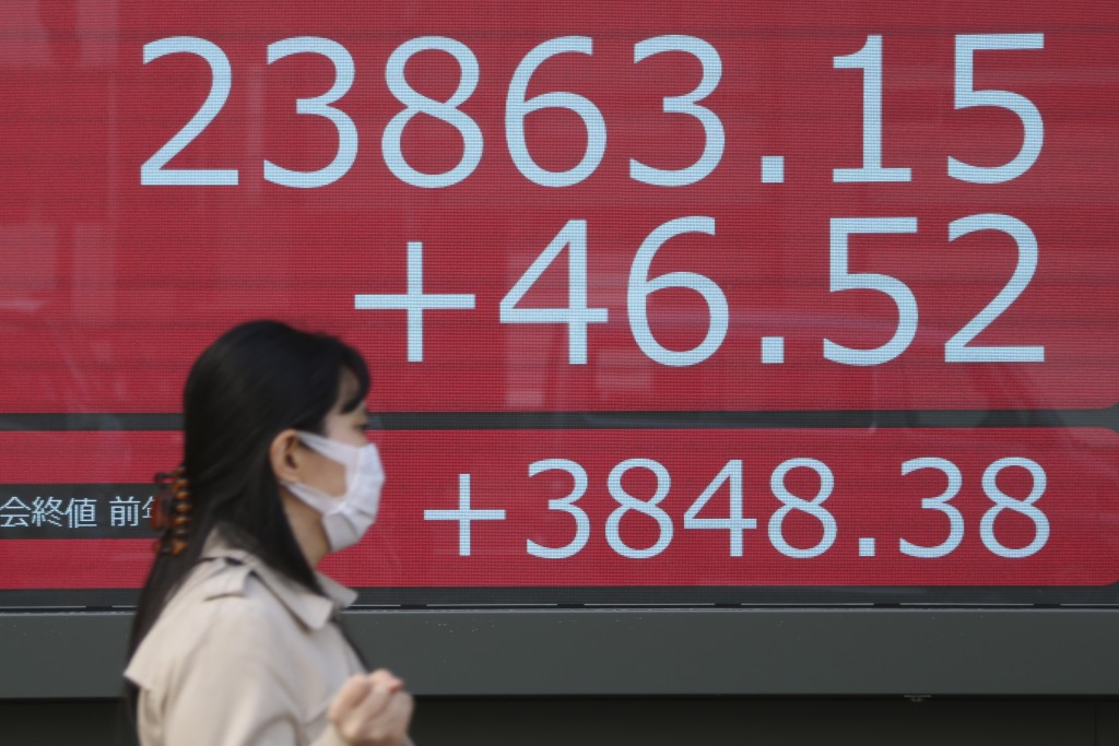 A woman walks by an electronic stock board of a securities firm in Tokyo, Monday, Dec. 23, 2019. Shares were mixed Monday in quiet trading ahead of Ch...