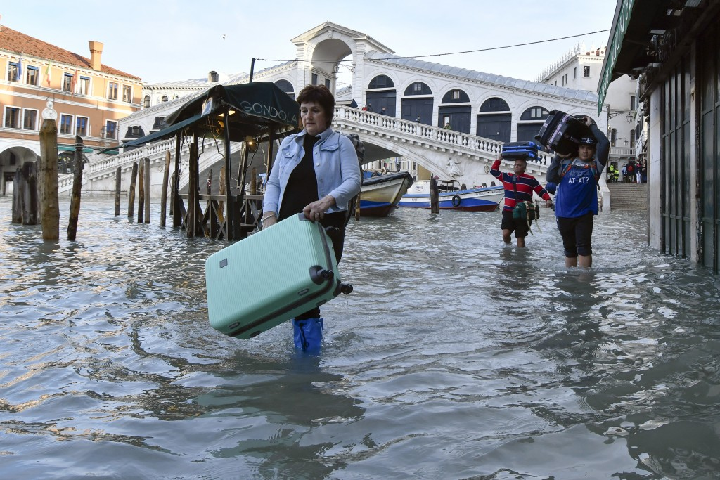 People carry their luggage as they wade through water during a high tide of 1.44 meters (4.72 feet), near the Rialto Bridge, in Venice, Italy, Monday,...