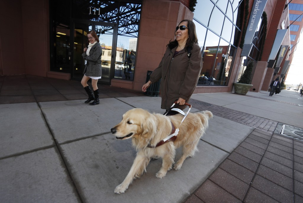 In this Dec. 13, 2019, photograph, Colorado Springs, Colo., city council member Yolanda Avila is led by her seeing eye dog along the streets of downto...