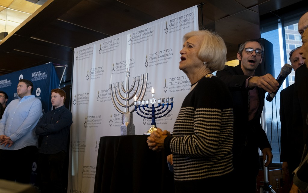 As a menorah is lighted, symbolizing the first day of Hanukkah, survivors of the Holocaust and other participants gather at the Museum of Jewish Herit...