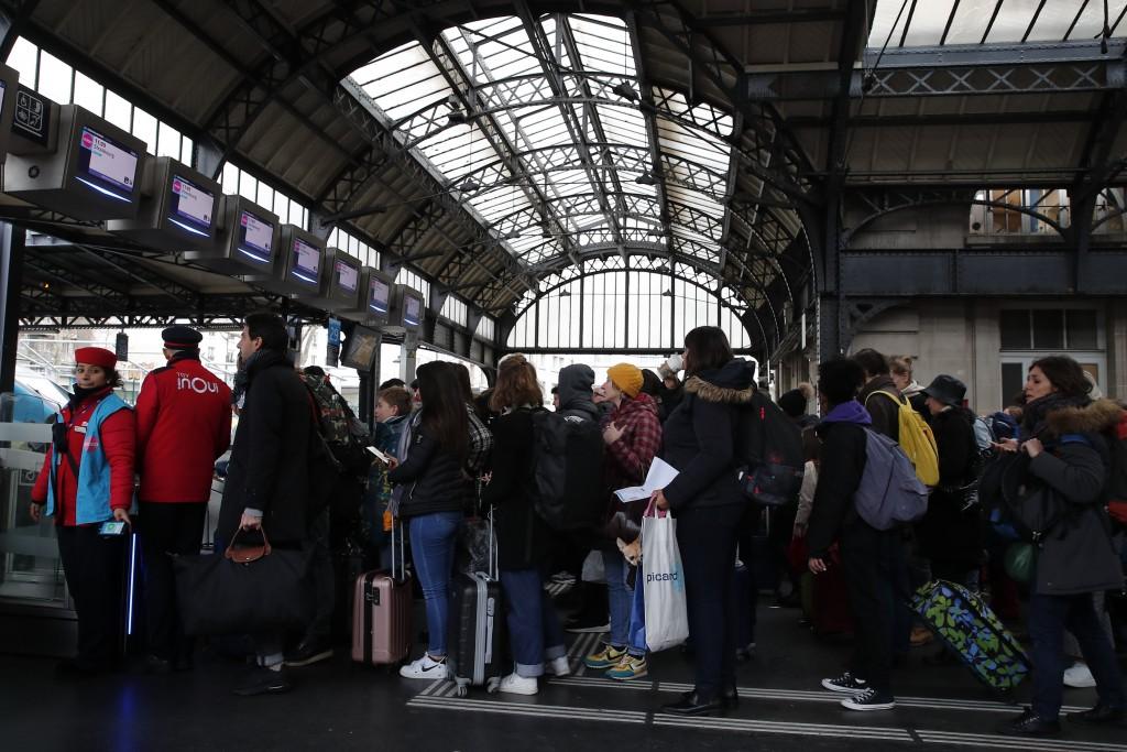 People queue to enter a platform at the Gare de l'Est train station Monday, Dec. 23, 2019 in Paris. France's punishing transportation troubles may eas...