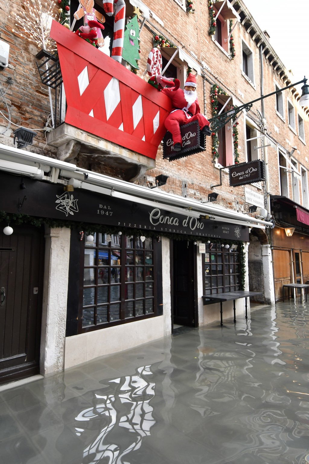 Christmas decorations adorn a restaurant as water floods the street during a high tide of 1.44 meters (4.72 feet), in St. Mark's Square, in Venice, It...