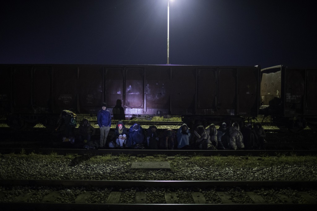 In this picture taken Monday Dec. 16, 2019, a group of migrants wait to be identified after being detained by Bosnian police around the the river Drin...