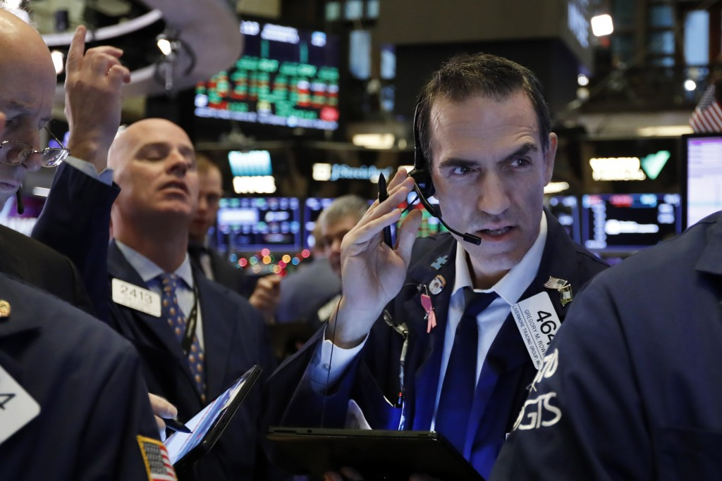 FILE - In this Dec. 11, 2019, file photo trader Gregory Rowe, right, works on the floor of the New York Stock Exchange. The U.S. stock market opens at...