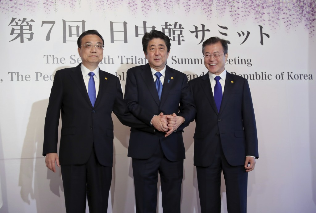 FILE- In this May 9, 2018, file photo, Chinese Premier Li Keqiang, left, Japanese Prime Minister Shinzo Abe, center, and South Korean President Moon J...
