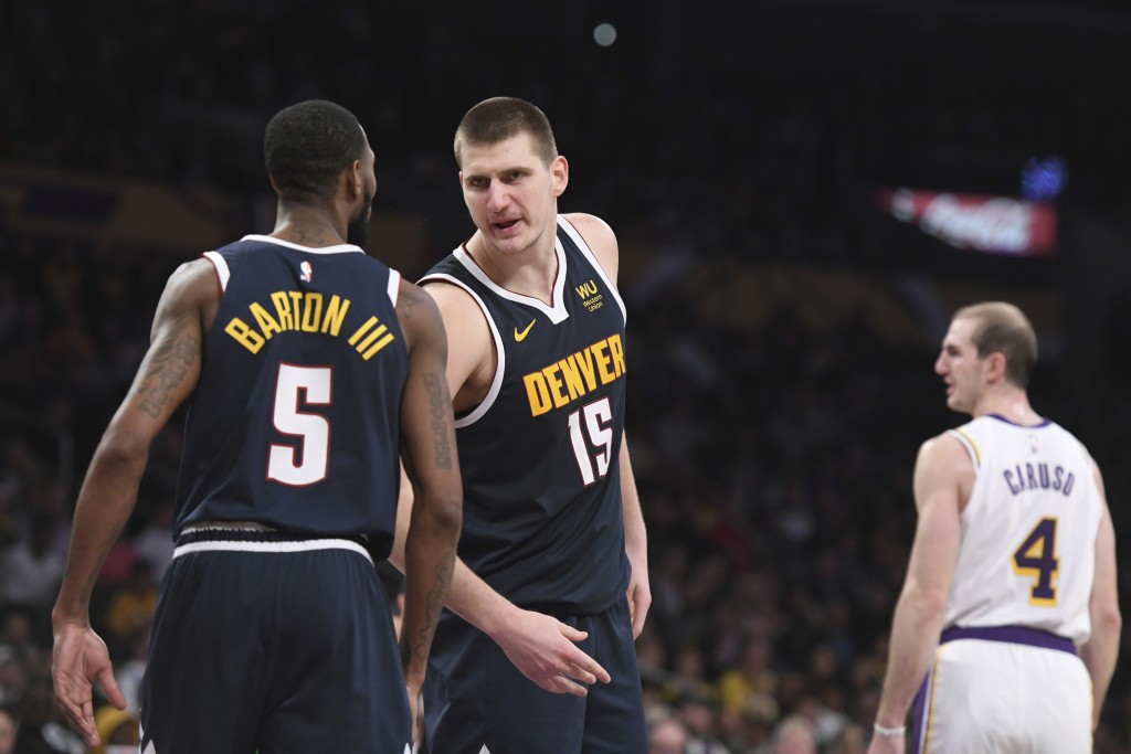 Denver Nuggets center Nikola Jokic (15) talks with forward Will Barton III (5) after Jokic was fouled during the second half of an NBA basketball game...