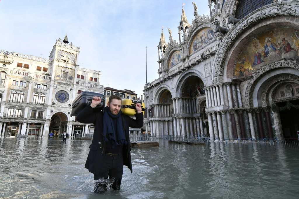 A man carries suitcases as he wades through water during a high tide of 1.44 meters (4.72 feet), in St. Mark's Square, in Venice, Italy, Monday, Dec. ...