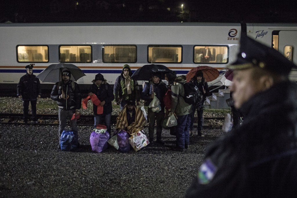 In this picture taken Saturday Dec. 14, 2019, a group of Pakistani migrants stands by the rail tracks after being taken off a train bound to the town ...
