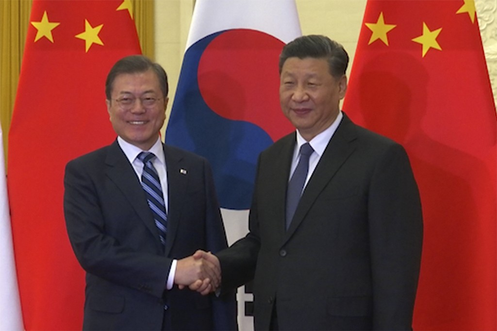 In this image from video, South Korean President Moon Jae-in, left, shakes hands with his Chinese counterpart Xi Jinping as they pose for photographer...