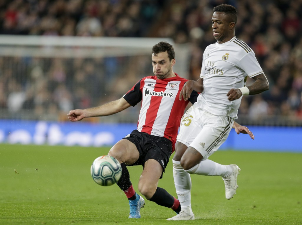 Real Madrid's Vinicius Junior, front, is tackled by Athletic Bilbao's Inigo Lekue during a Spanish La Liga soccer match between Real Madrid and Athlet...
