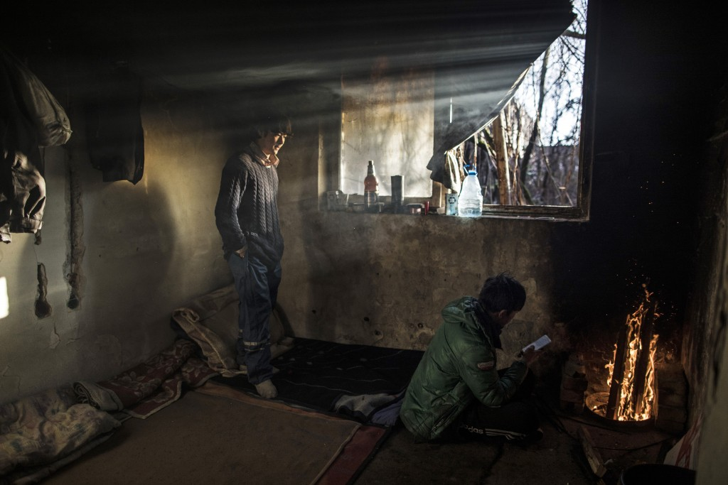 In this picture taken Saturday Dec. 14, 2019, Afghan migrants warm up inside an abandoned factory used by migrants as shelter, before making another a...