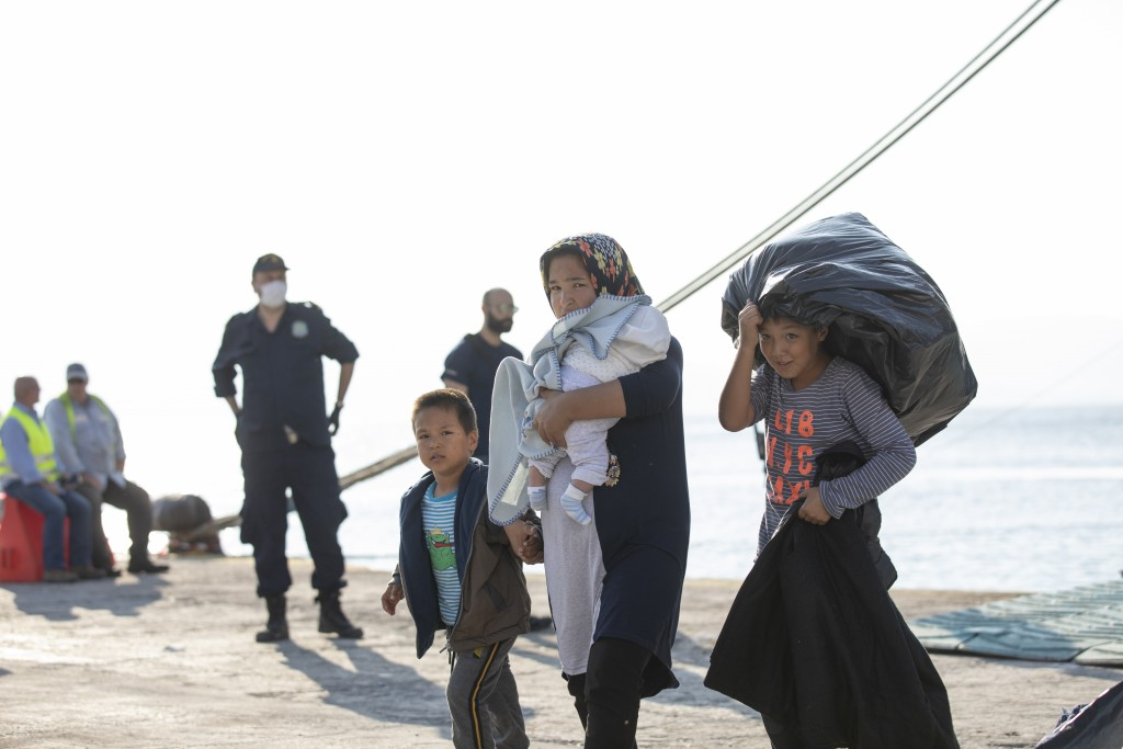 FILE - In this Tuesday, Oct. 22, 2019 file photo refugees and migrants disembark from a ferry at the port of Elefsina, near Athenss, Greece. The Germa...