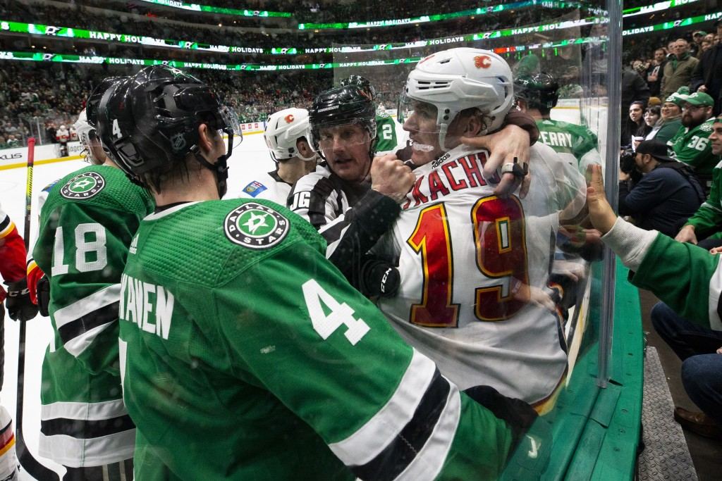 Dallas Stars defenseman Miro Heiskanen (4) and Calgary Flames left wing Matthew Tkachuk (19) are separated by an official during the second period of ...