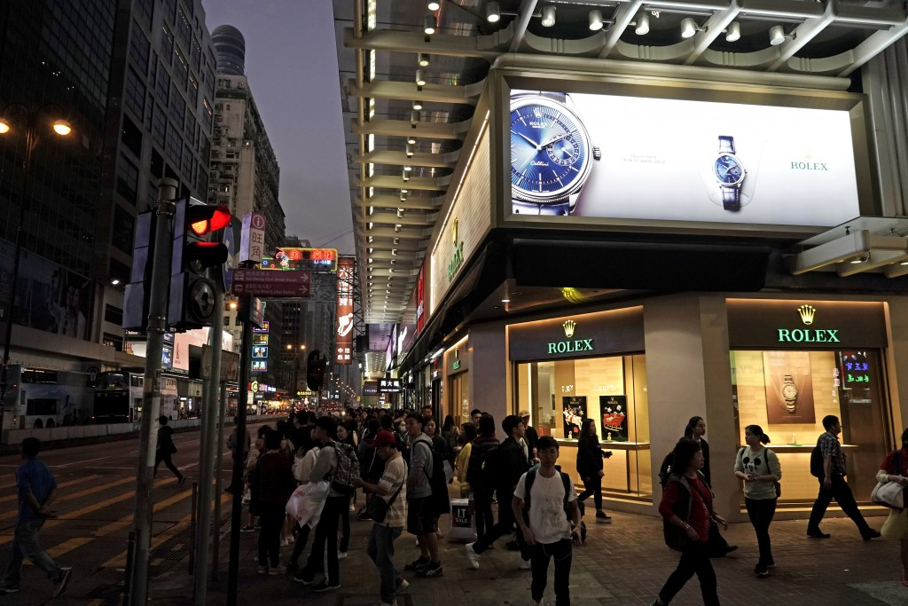 In this Wednesday, Dec. 18, 2019, photo, people walk past a luxury watch shop on a main street in Mongkok, a shopping district of Hong Kong. Sellers o...