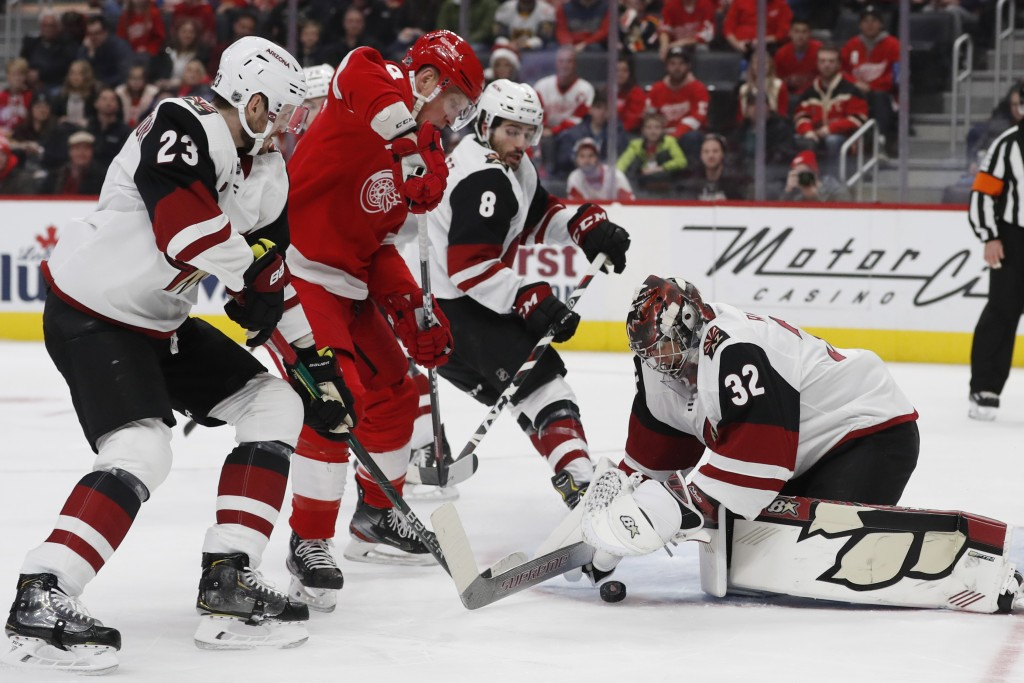 Arizona Coyotes goaltender Antti Raanta (32) falls on the puck hit by Detroit Red Wings left wing Justin Abdelkader (8) during the first period of an ...
