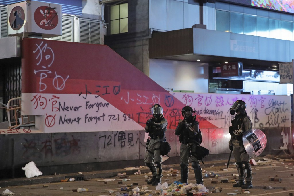 In this Monday, Nov. 11, 2019, photo, riot police stand guard in Mongkok, a shopping district of Hong Kong. Sellers of luxury goods that are easily pe...