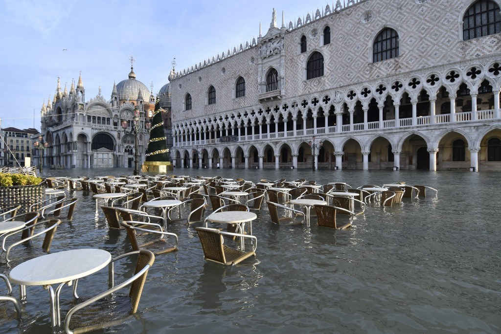 Cafè tables and chairs are partially covered in water during a high tide of 1.44 meters (4.72 feet), in St. Mark's Square, in Venice, Italy, Monday, D...