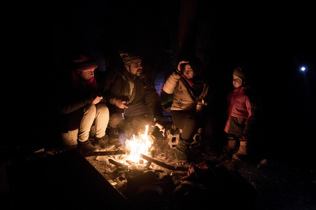 In this picture taken Thursday Dec. 12, 2019, Indian migrants Nishademi, 22, and Suhil, 23, warm up by a fire next to Fatma, 24, and her son Omar, 1, ...