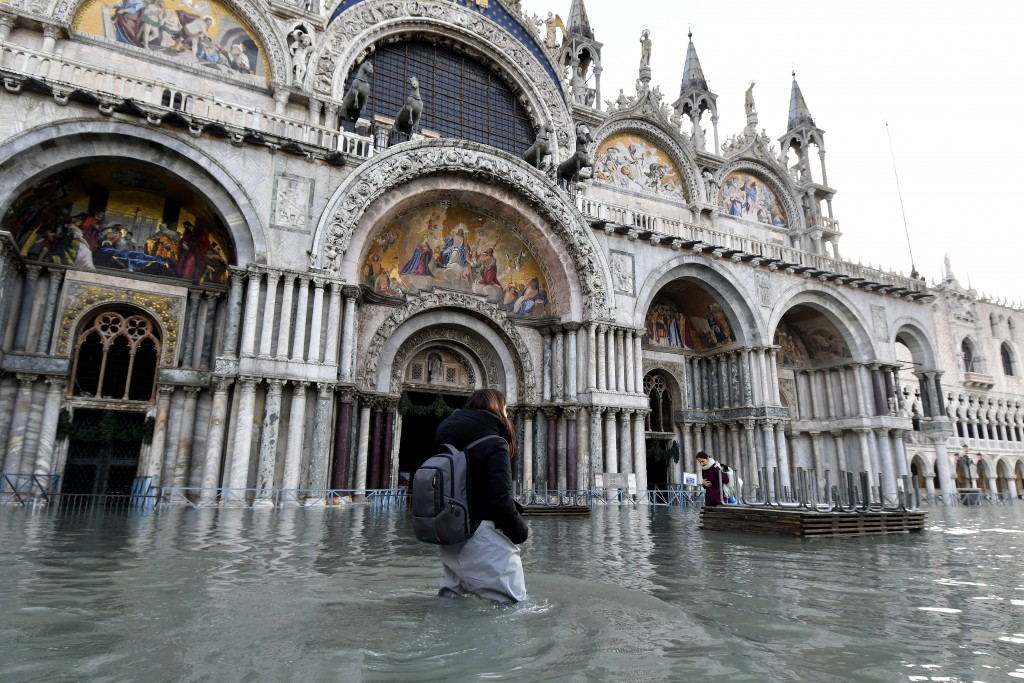 A woman wades through water during a high tide of 1.44 meters (4.72 feet), in St. Mark's Square, in Venice, Italy, Monday, Dec. 23, 2019. Venice is fa...