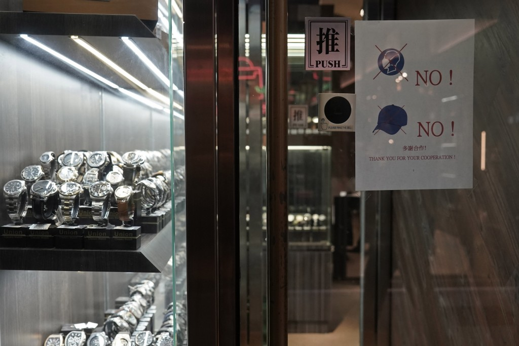 In this Wednesday, Dec. 18, 2019, photo, a notice is attached to the front door demanding no hats and masks allowed in the watch store to help prevent...