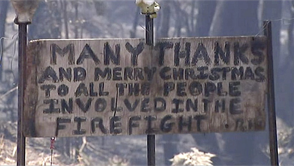 In this image made from video, a sign offers thanks and a Merry Christmas in a destroyed residential area by wildfire, Monday, Dec. 23, 2019, in the B...