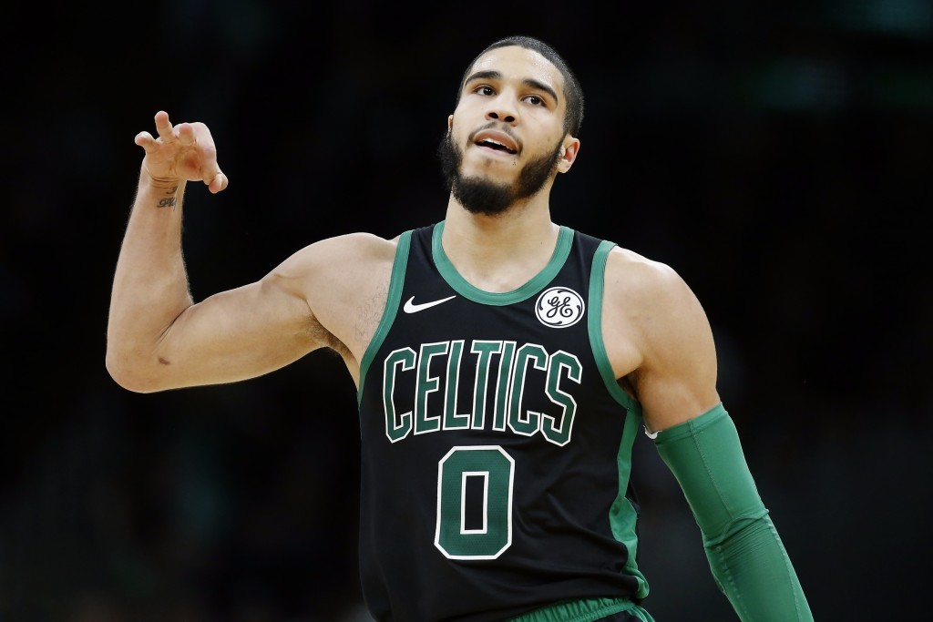 Boston Celtics' Jayson Tatum reacts after making a three-point basket during the second half of an NBA basketball game against the Charlotte Hornets i...