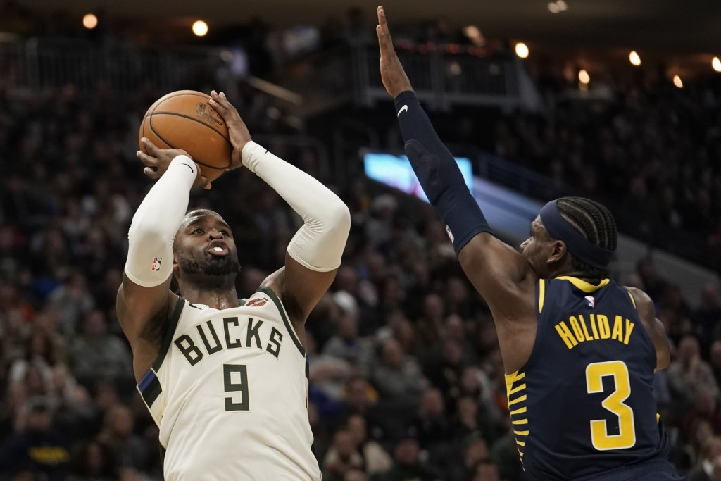 Milwaukee Bucks' Wesley Matthews shoots past Indiana Pacers' Aaron Holiday during the first half of an NBA basketball game Sunday, Dec. 22, 2019, in M...