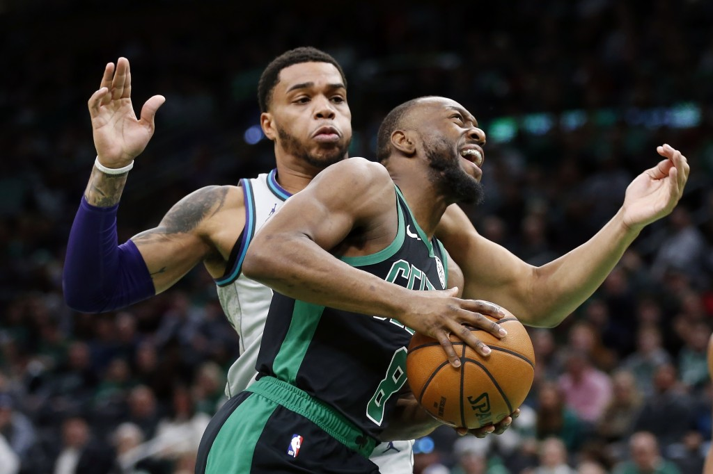 Boston Celtics' Kemba Walker (8) drives past Charlotte Hornets' Miles Bridges during the first half of an NBA basketball game in Boston, Sunday, Dec. ...