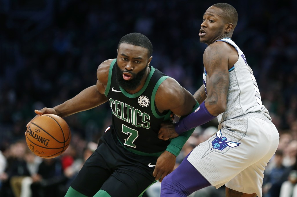 Boston Celtics' Jaylen Brown (7) drives past Charlotte Hornets' Terry Rozier, right, during the first half of an NBA basketball game in Boston, Sunday...