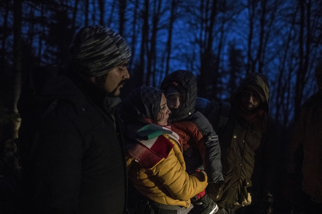 In this picture taken Thursday Dec. 12, 2019, Indian migrant Suhil, 23, helps Syrian migrant Fatma, 24, to hold her son Omar, 1, while crossing the mo...