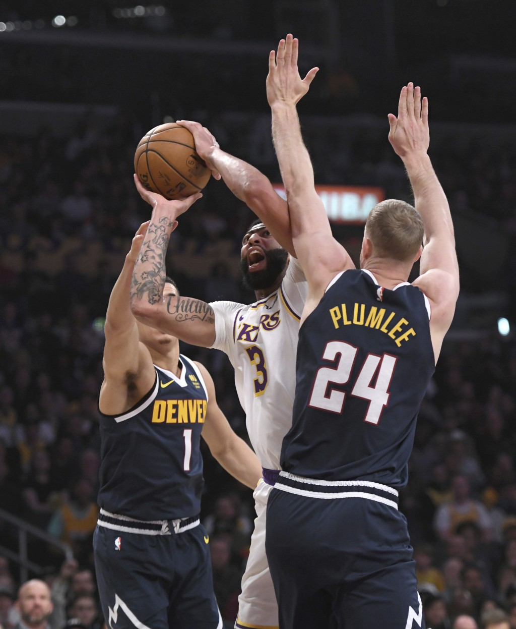 Los Angeles Lakers forward Anthony Davis is fouled as he shoots between Denver Nuggets forward Michael Porter Jr., left, and center Mason Plumlee duri...