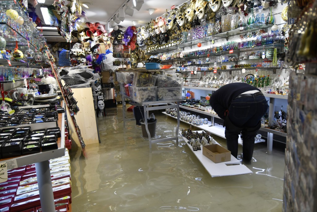 A shop keeper checks the damages after a high tide of 1.44 meters (4.72 feet) flooded a souvenir shop, in Venice, Italy, Monday, Dec. 23, 2019. Venice...